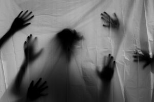 White sheet with the silhouette of hands and a body behind it.